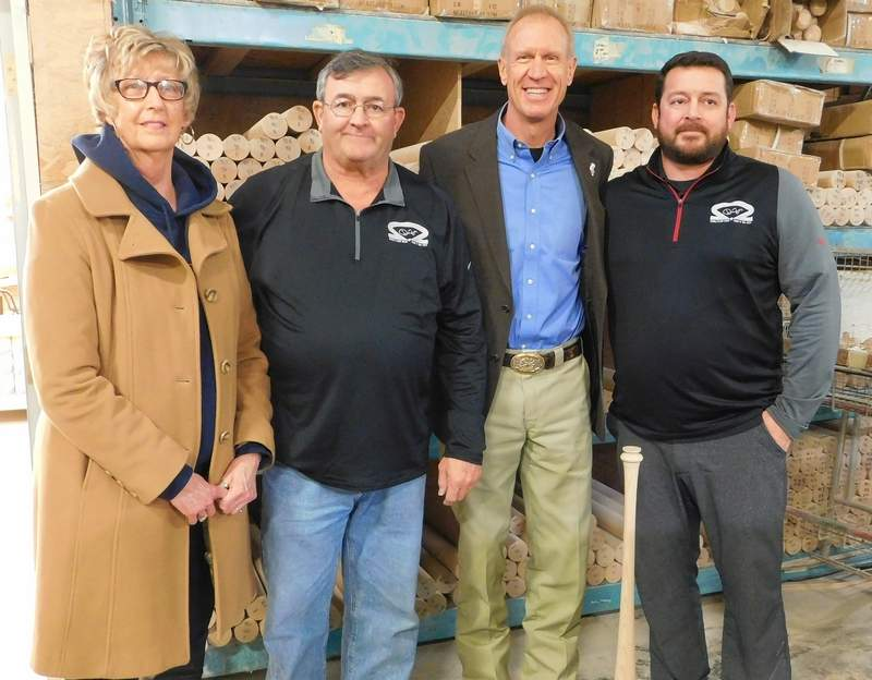 From left, Ridgway Mayor Rebecca Mitchell, Randy Drone, Gov. Bruce Rauner, and Kyle Drone pose for a photo in front of stacks of maple that will become Dinger bats.