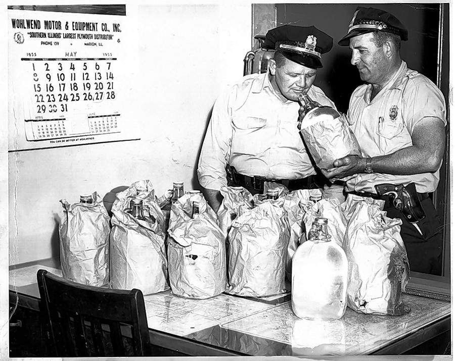 """Confiscated moonshine alcohol is checked by Marion Deputy Jack Stephens, left, and Chief of Police Charles """"Yobbie"""" Edwards at Marion Police Department headquarters in 1955."""