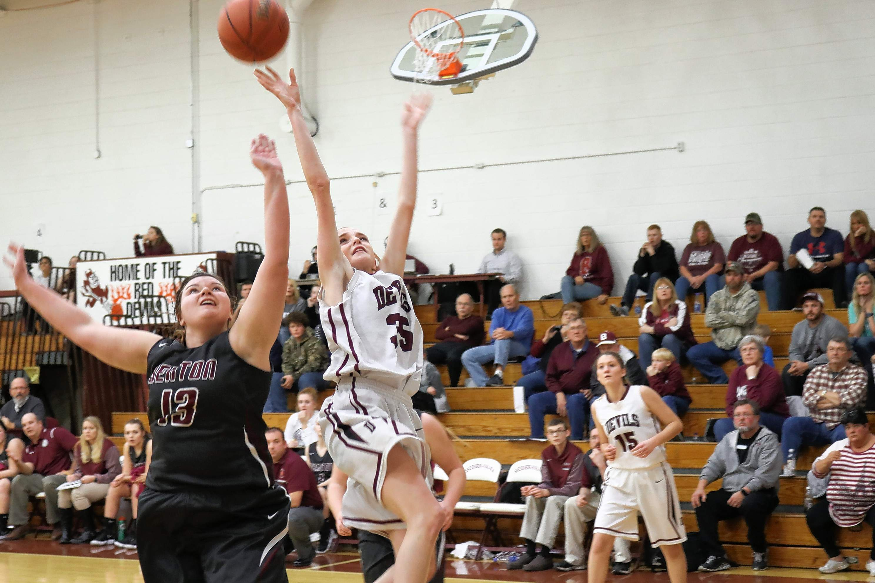 Paige Tucker (white jersey) of the Red Devils goes up for a shot against Benton's Macie Cockrum in last week's home game with Benton.
