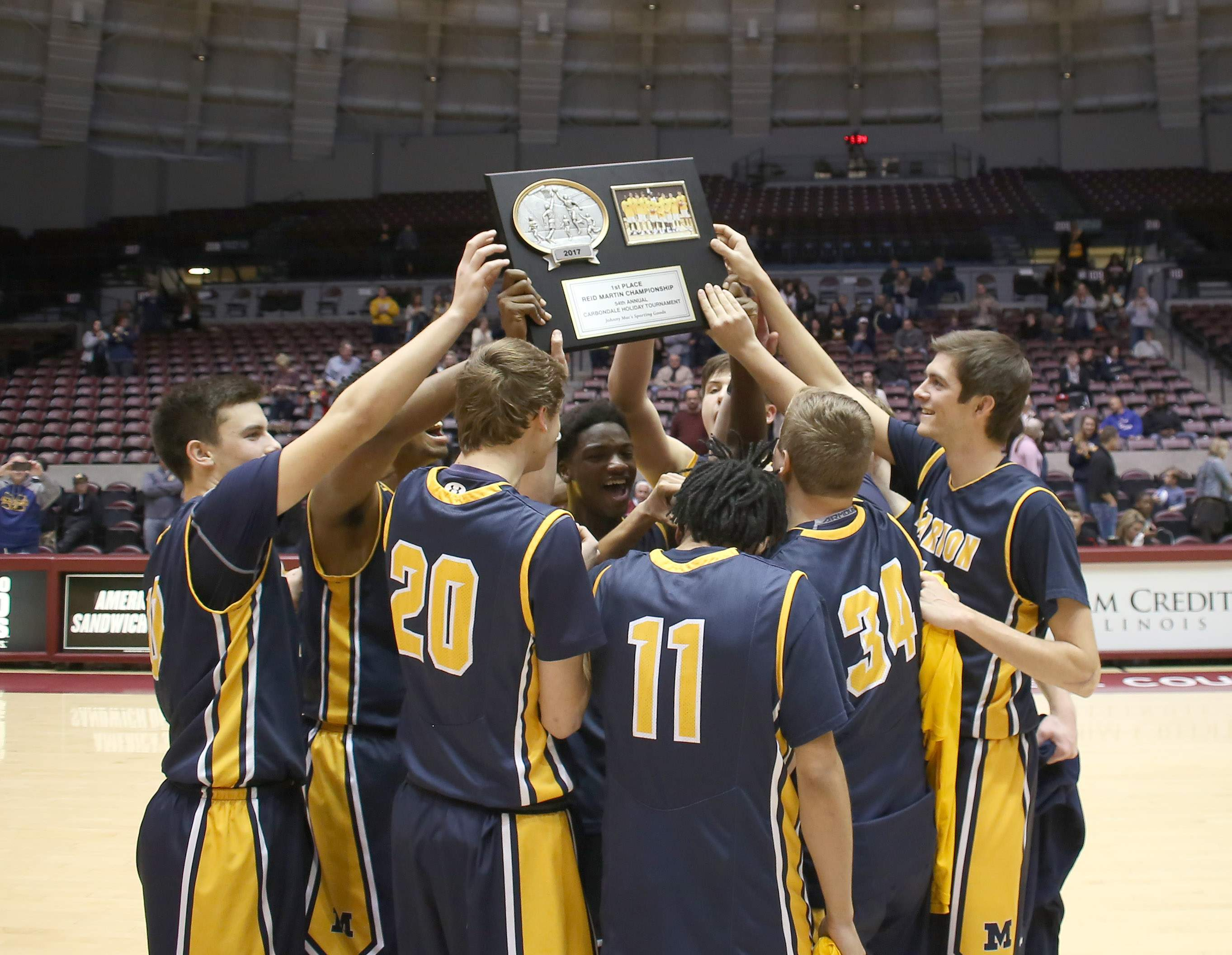 The Marion Wildcats accept the Championship Plus trophy at the 54th annual Carbondale Holiday Tournament on Friday night at SIU Arena.