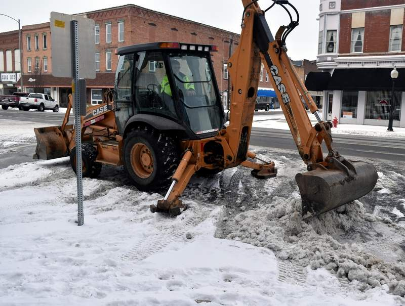 A City of Du Quoin Street Department worker removes snow from parking spaces on Main Street on Tuesday. According to the National Weather Service, January's average temperature thus far is 10 and a half degrees below normal.
