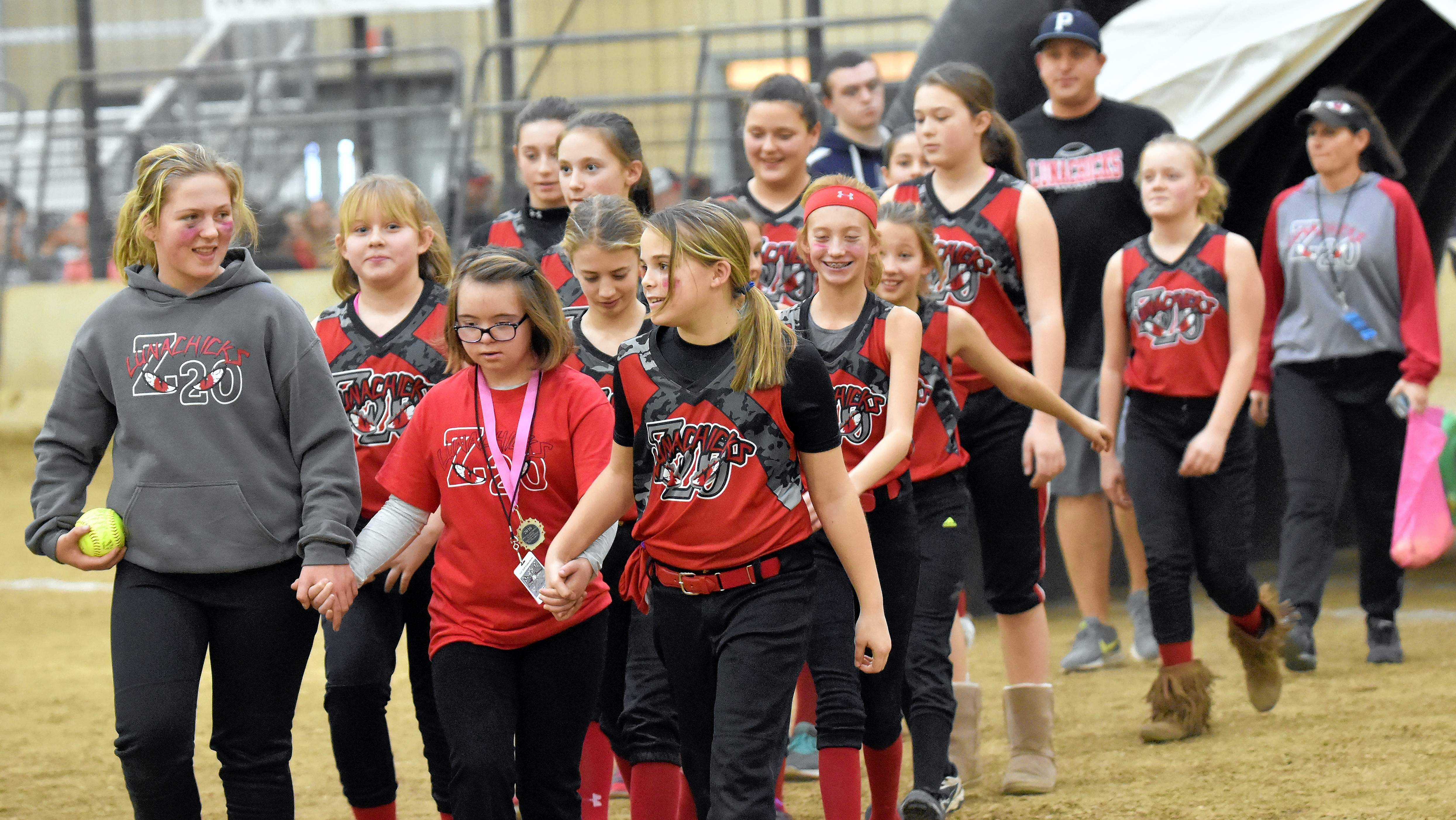 The 12-and-under Z20 Lunachicks, based out of Pinckneyville, enter the field during Saturday's opening ceremonies of the Indoor Softball Girls Fastpitch Tournament with their Special Olympics athlete Addi Williams, of Du Quoin.