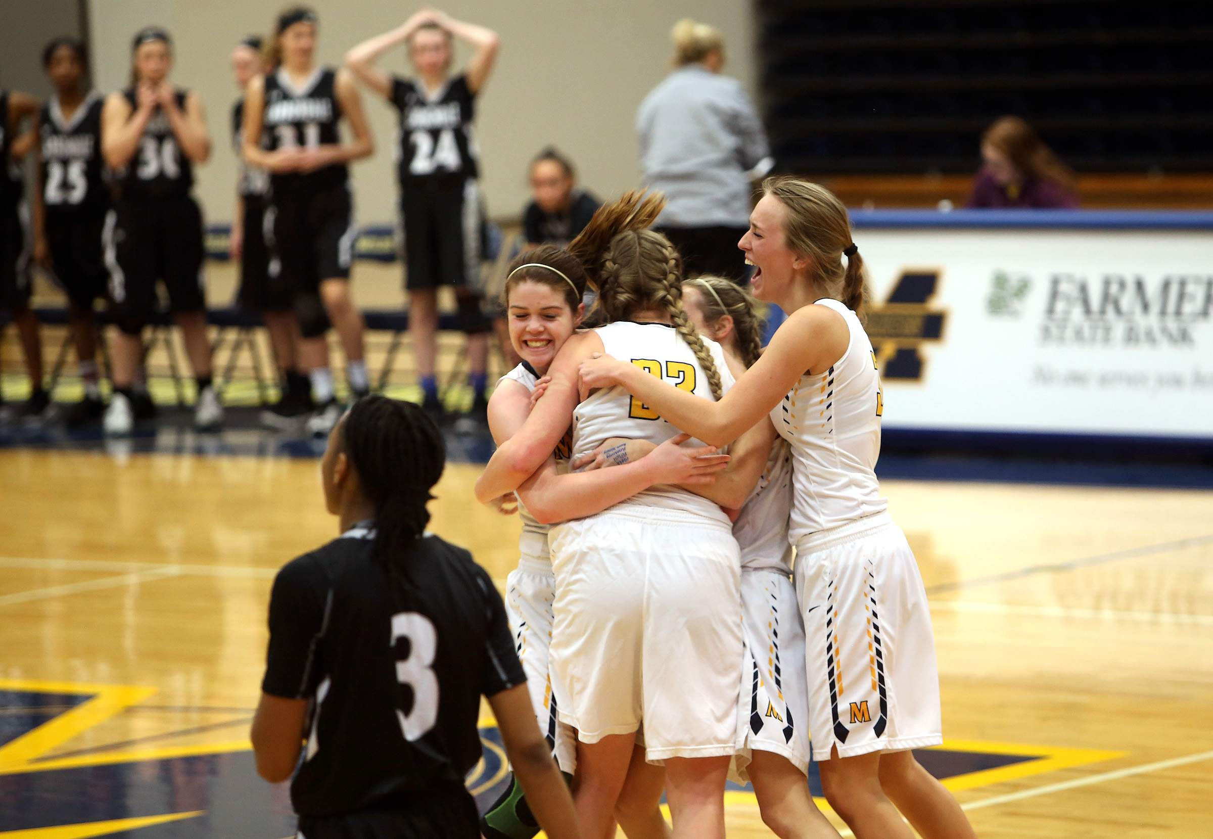 Marion seniors Abby Bayer (left) and Jasa Bell (right) hug juniors McKenzie Orange and Lauryn Kadela after the buzzer Thursday night.