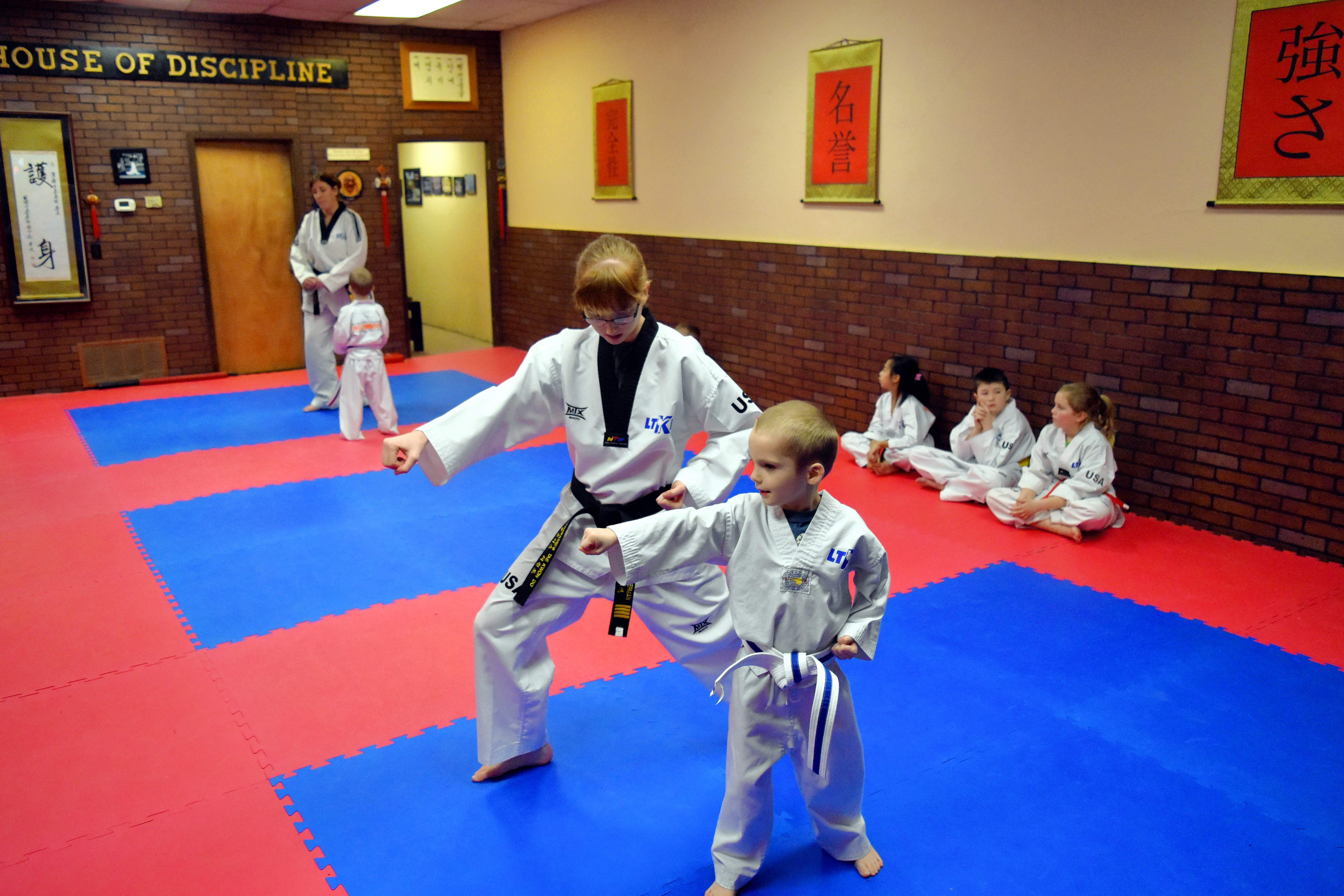 "Student Patsy Lipe helps a young student with his stance during the ""Little Ninjas"" class on Tuesday."
