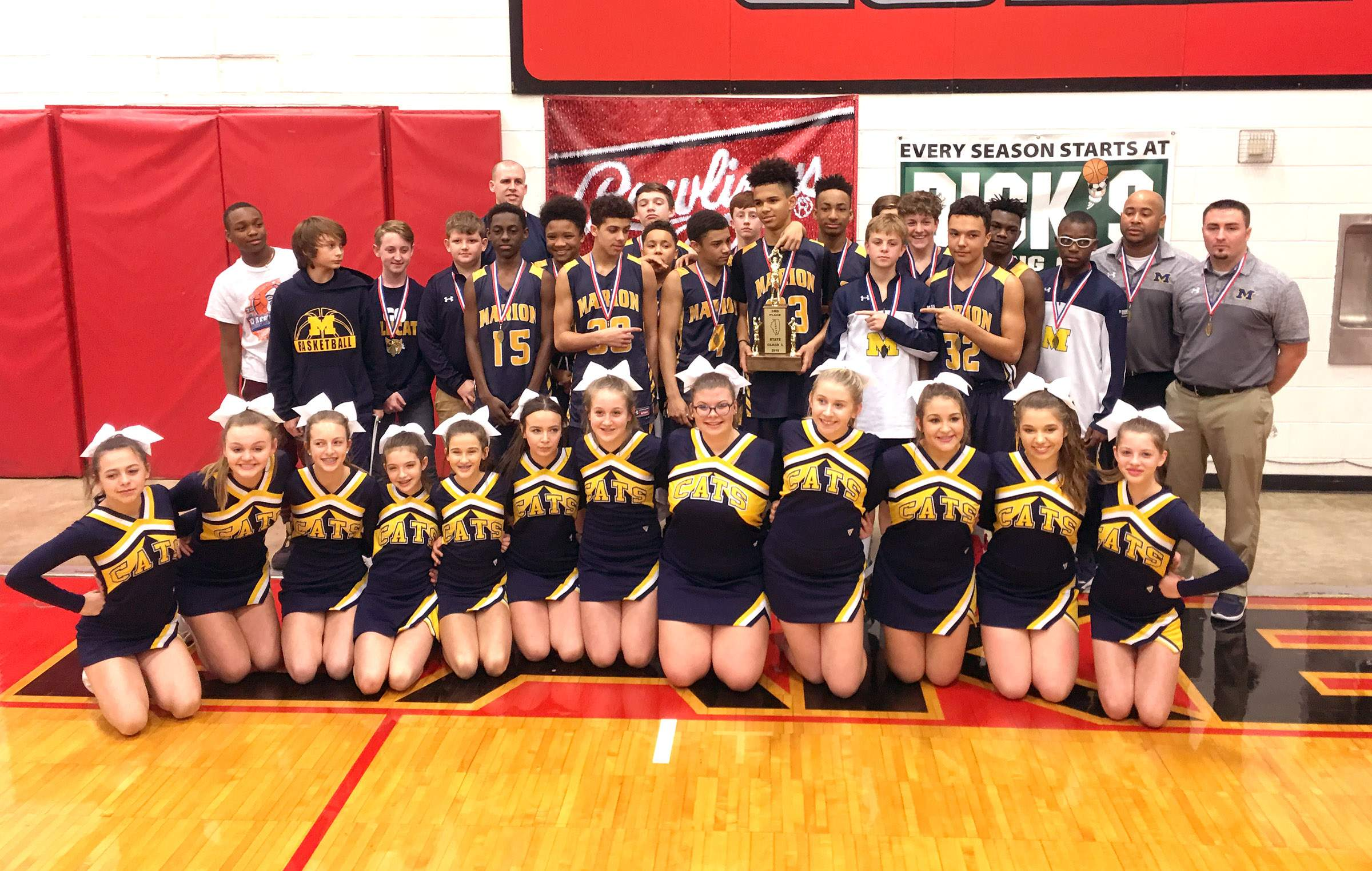 The Marion Junior High School boys basketball team and cheerleaders pose with the Class L third place trophy.