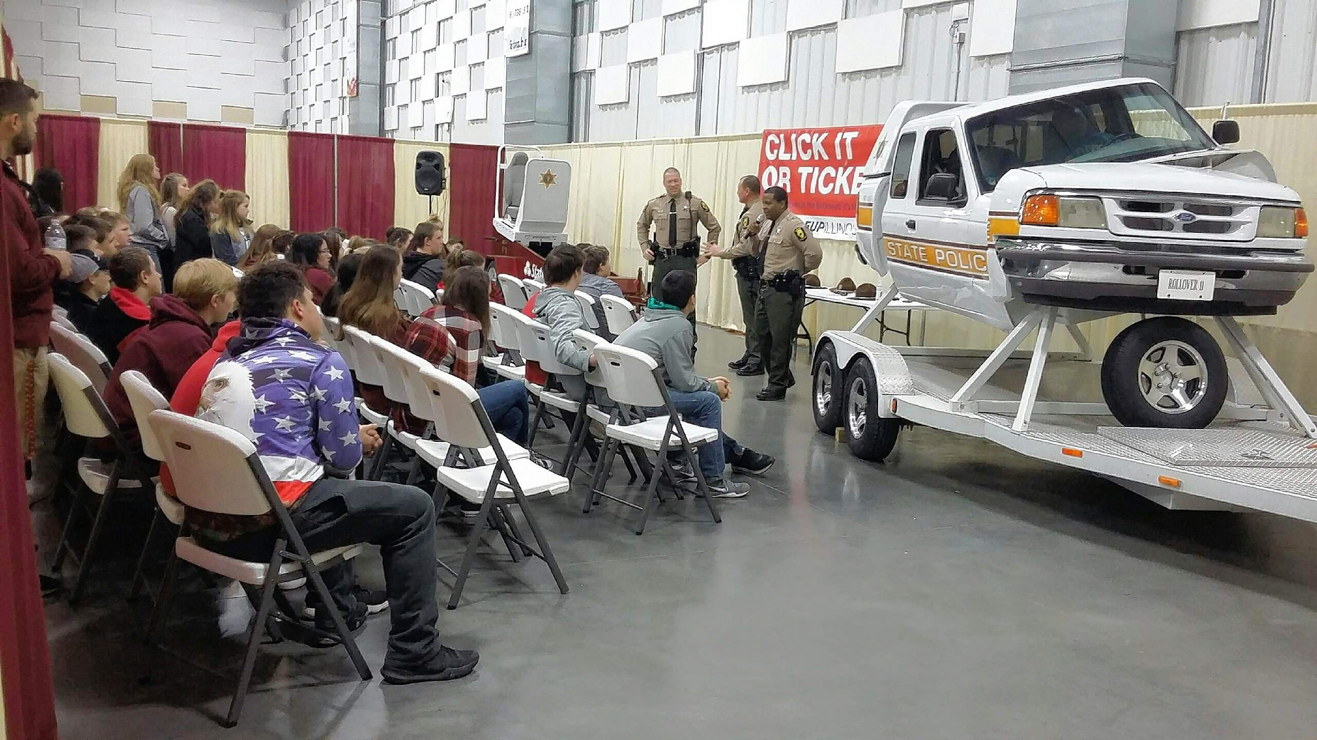 Benton High School students and their driver's ed teacher, Aaron Webb, (far left) are impressed by the 'Seat Belt Convincer' rollover demonstration.