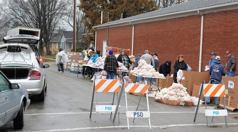 Nearly 100 vehicles lined up around at least eight city blocks Tuesday morning leading to the South Douglas Street food pantry, where approximately 100,000 pounds of food was delivered by the St. Louis Food Bank. At top, a truck was filled to the brim with food supplies that were distributed to a couple hundred area residents Tuesday morning at the Pinckneyville food pantry.