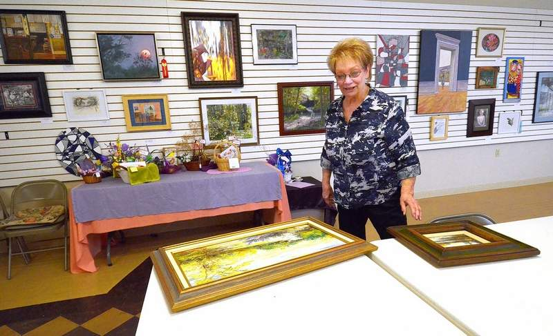 LEAA member Brenda Fleming of Pittsburg looks over some of the entrants in the competition at Saturday's writing and painting reception and awards ceremony.
