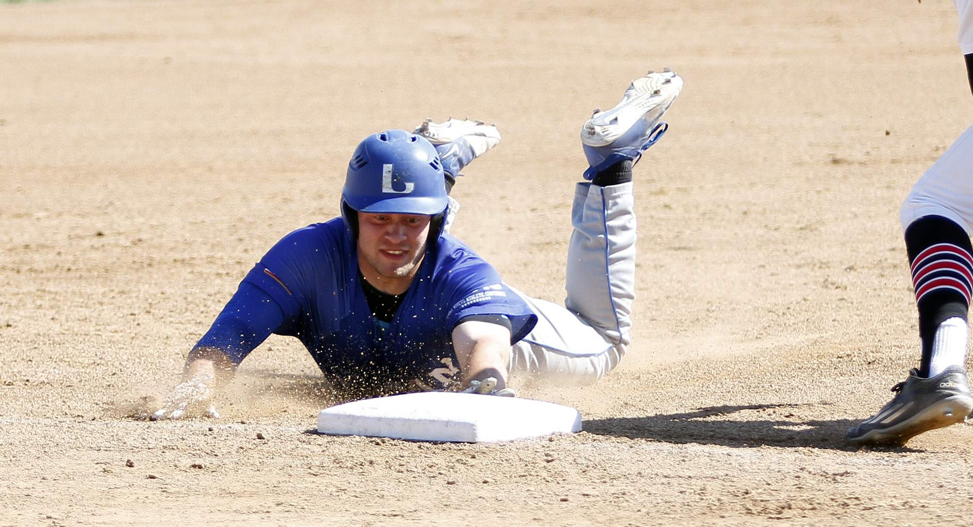 Hunter Combs dives into third base Saturday.