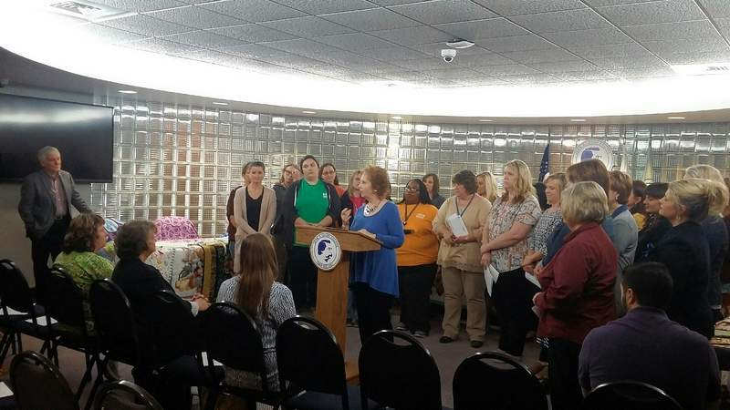 Glenn Poshard, far left, looks on as his wife, Jo Poshard, surrounded by grant recipients from the Poshard Foundation for Abused Children, addresses the audience at the JALC news conference Monday.