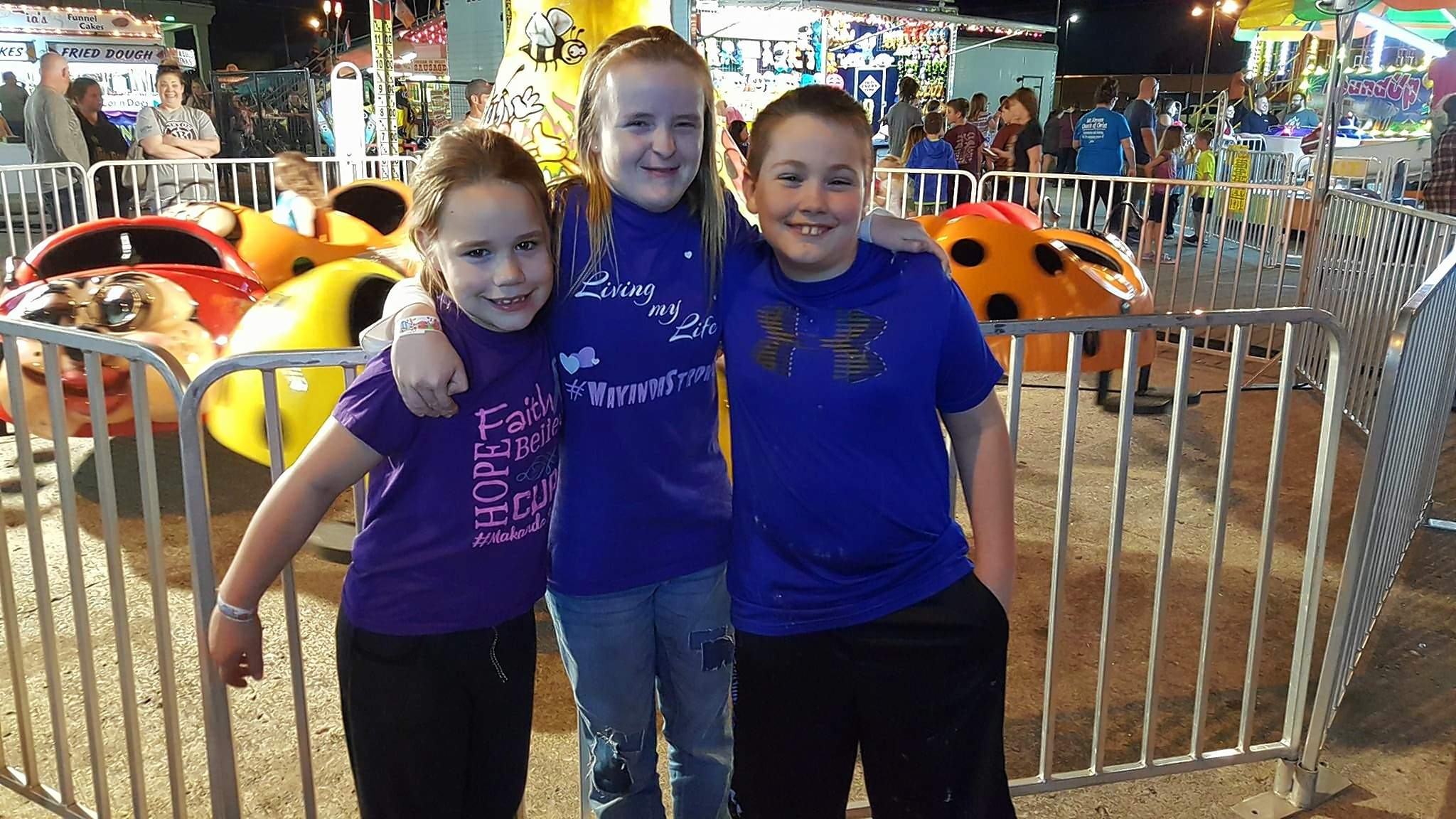 """Raylynn Alexander of Johnston City (middle) enjoyed the carnival on Friday evening courtesy of the family of Makanda Williams. The family, including Makanda's sister, Addie (left) and twin brother, Connor, treated three area children to arm bands and spending money for the carnival to kick off the """"Random Act of Kindness"""" campaign in honor of Makanda, who lost her battle to DIPG last week.  Friday would have been Makanda's 11th birthday."""