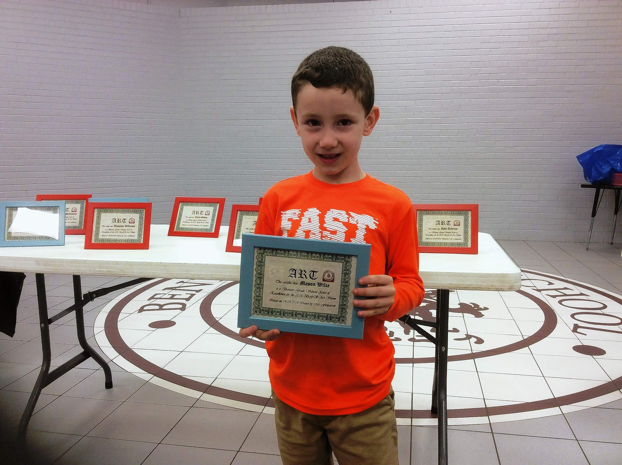 Mason Wilce stands with his Kindergarten Certificate of Excellence on April 28 at the Benton Middle School Gymnasium and Commons, where hundreds of K-8 works were on display.
