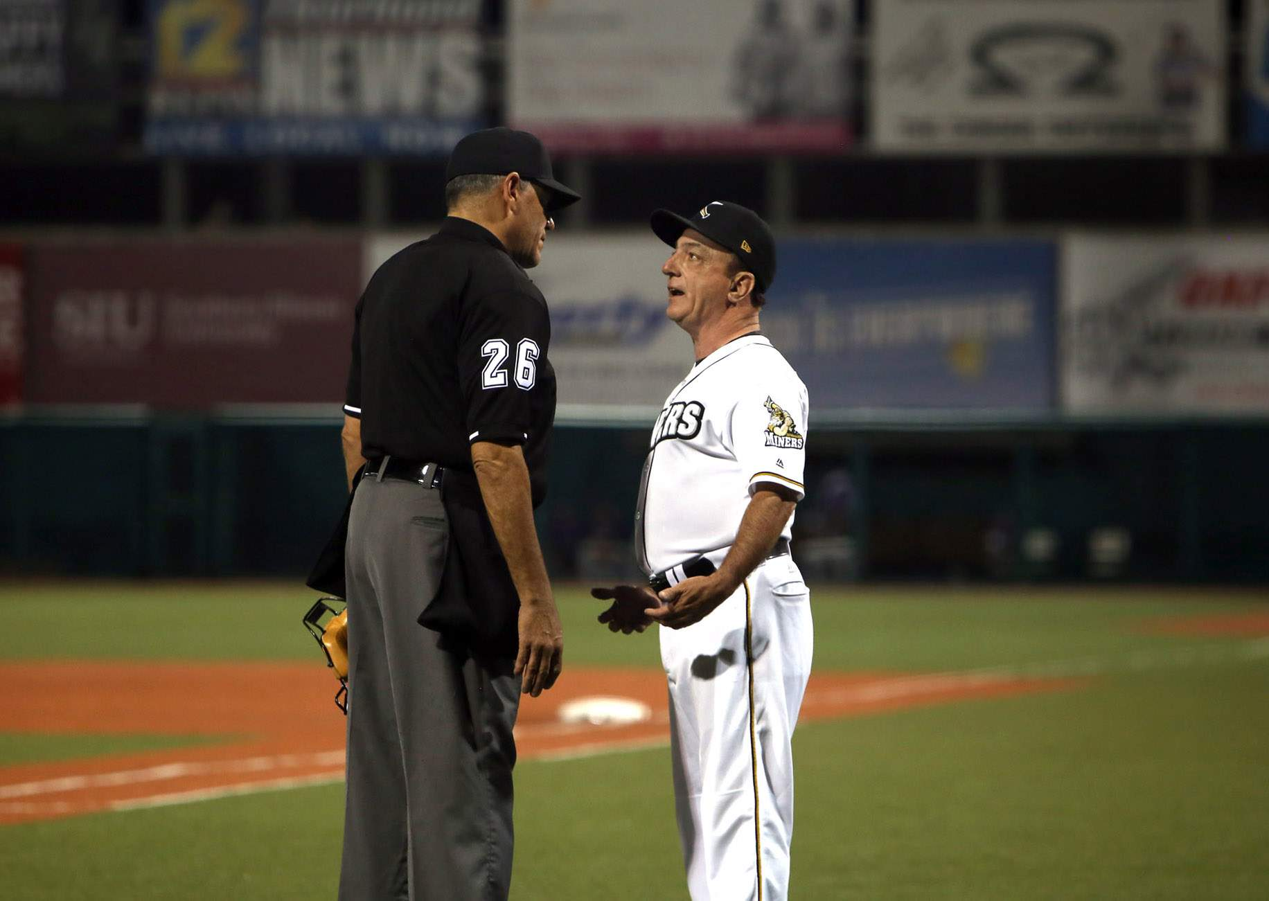 Miners manager Mike Pinto has a discussion with umpire Steve Bartelstein during the season opener.
