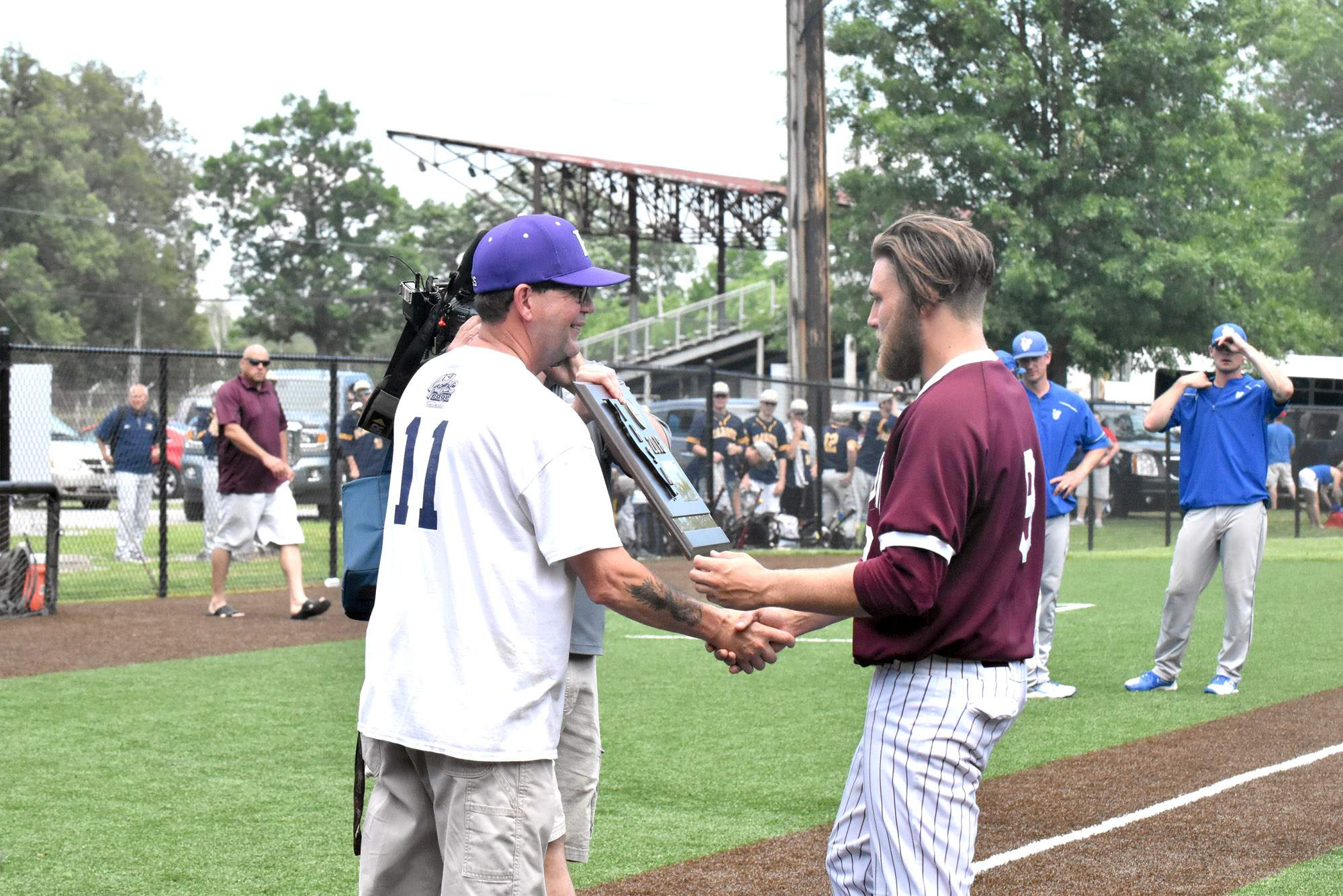 Benton senior Ian McMahon accepts the sectional plaque from Jay Thompson, head baseball coach of the host school Harrisburg, following the Rangers' 3-2 10-inning victory Saturday.