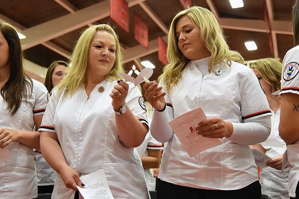Toward the end of RLC's ADN pinning ceremony on May 10, Alyssa (left) and Kara Jarvis light candles in honor of Florence Nightingale before reciting the Nightingale Pledge.