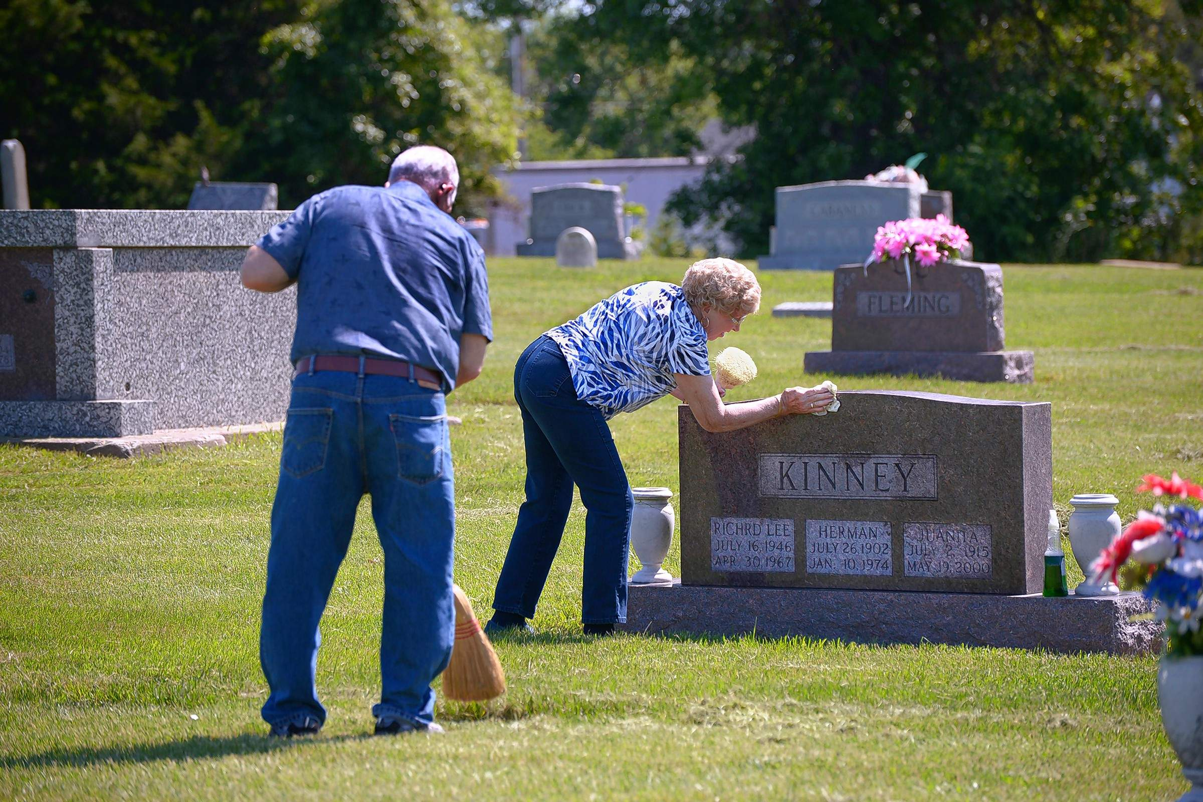 Jerry Kinney sweeps dried grass away from the brass foot marker of his late brother, Richard Lee, while his companion, Sue Orlowski, is busy cleaning the Vietnam War hero's tombstone at Rose Hill Cemetery in Marion just prior to the Memorial Day holiday.
