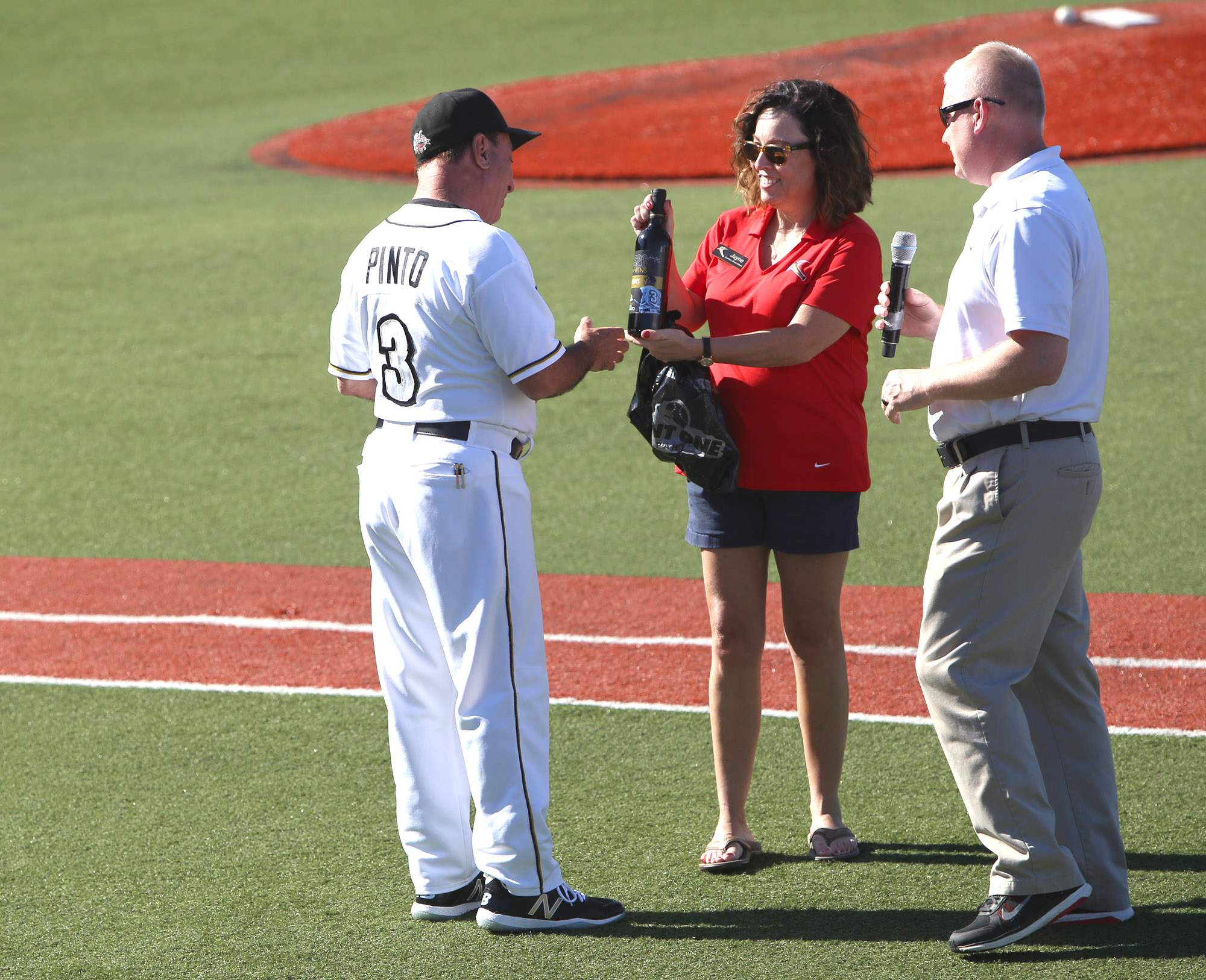 Miners manager Mike Pinto is presented a custom wine bottle from owner Jayne Simmons for becoming the Frontier League's all-time winningest manager.