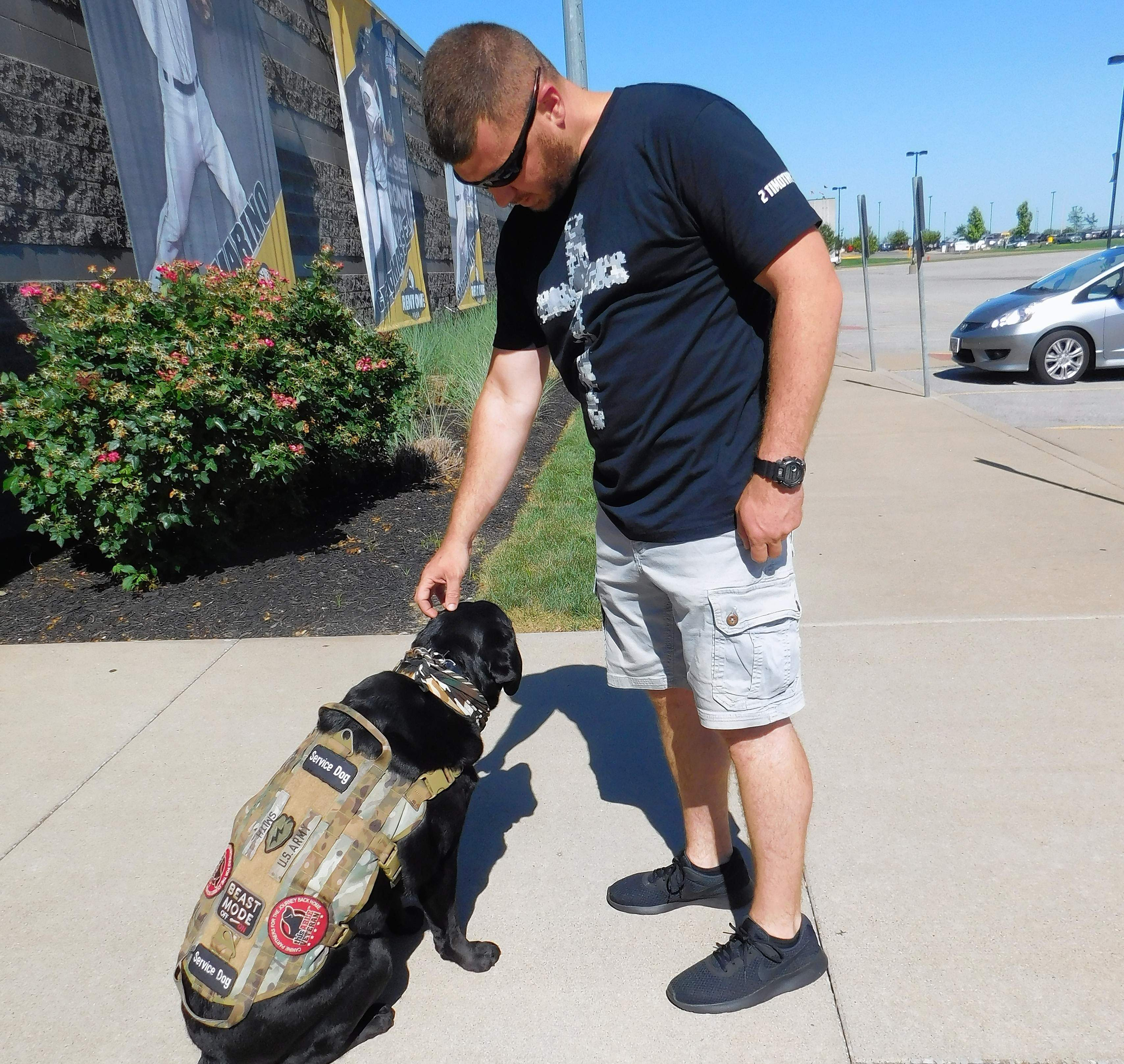 Jesse Smith of Du Quoin, gives his dog, Wyatt, a friendly head scratch.  Wyatt helps Smith to cope with his PTSD, nightmares, and anxiety.