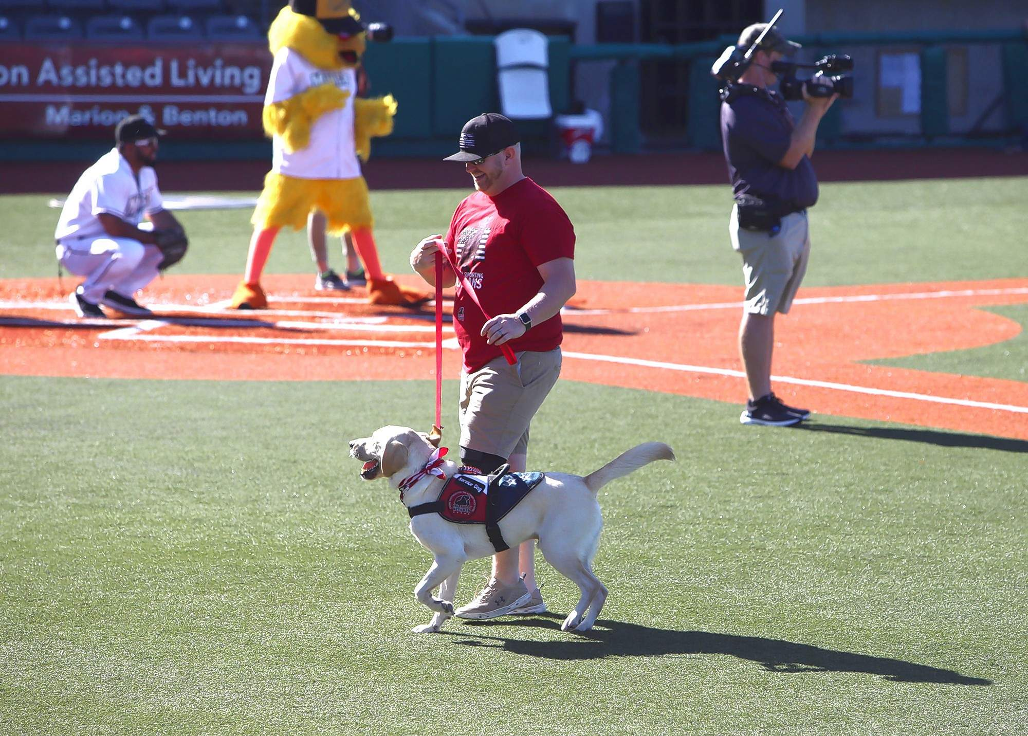 Veteran Sam Hoekstra of Carterville, with his canine buddy, 'Memphis,' got to throw out a first pitch at Sunday afternoon's Southern Illinois Miners game.
