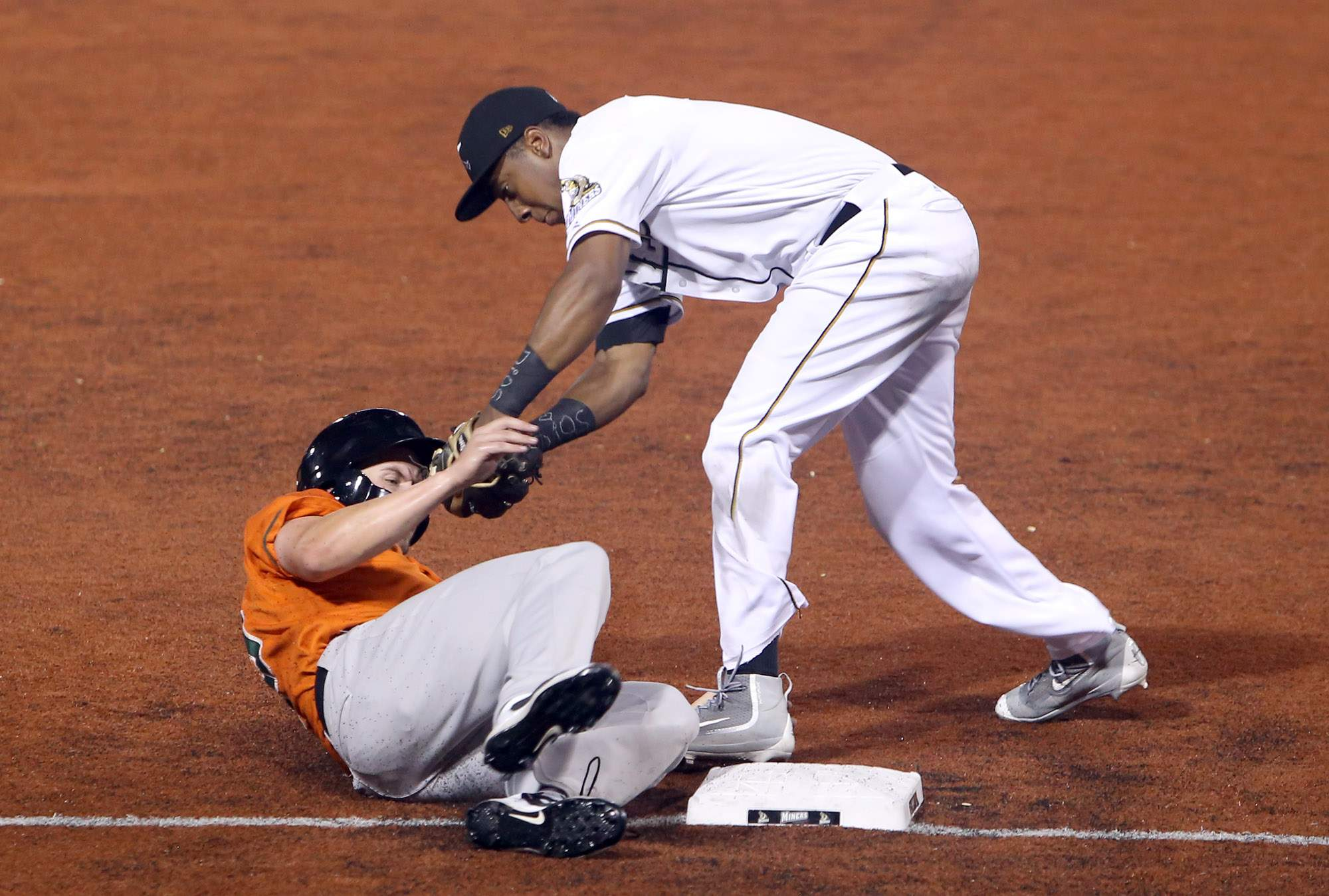 Miners third baseman Luis Jean tags out Joliet's Trenton Hill on a steal attempt Tuesday night.