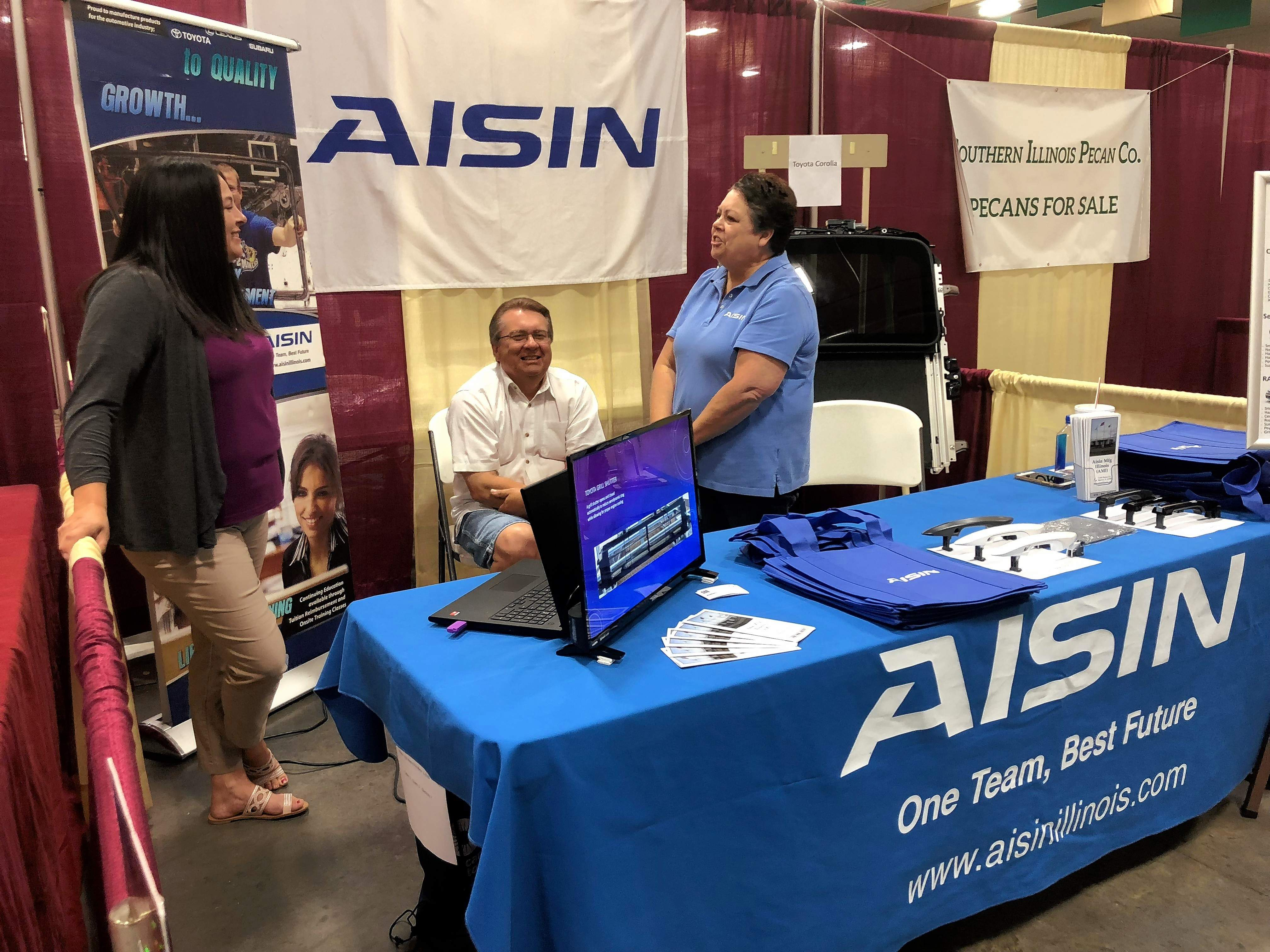 Bob Romonosky, middle, sits in as Renae Edwards, left, and Cheri Romonosky, right, of Aisin explain to visitors what their company contributes to southern Illinois.