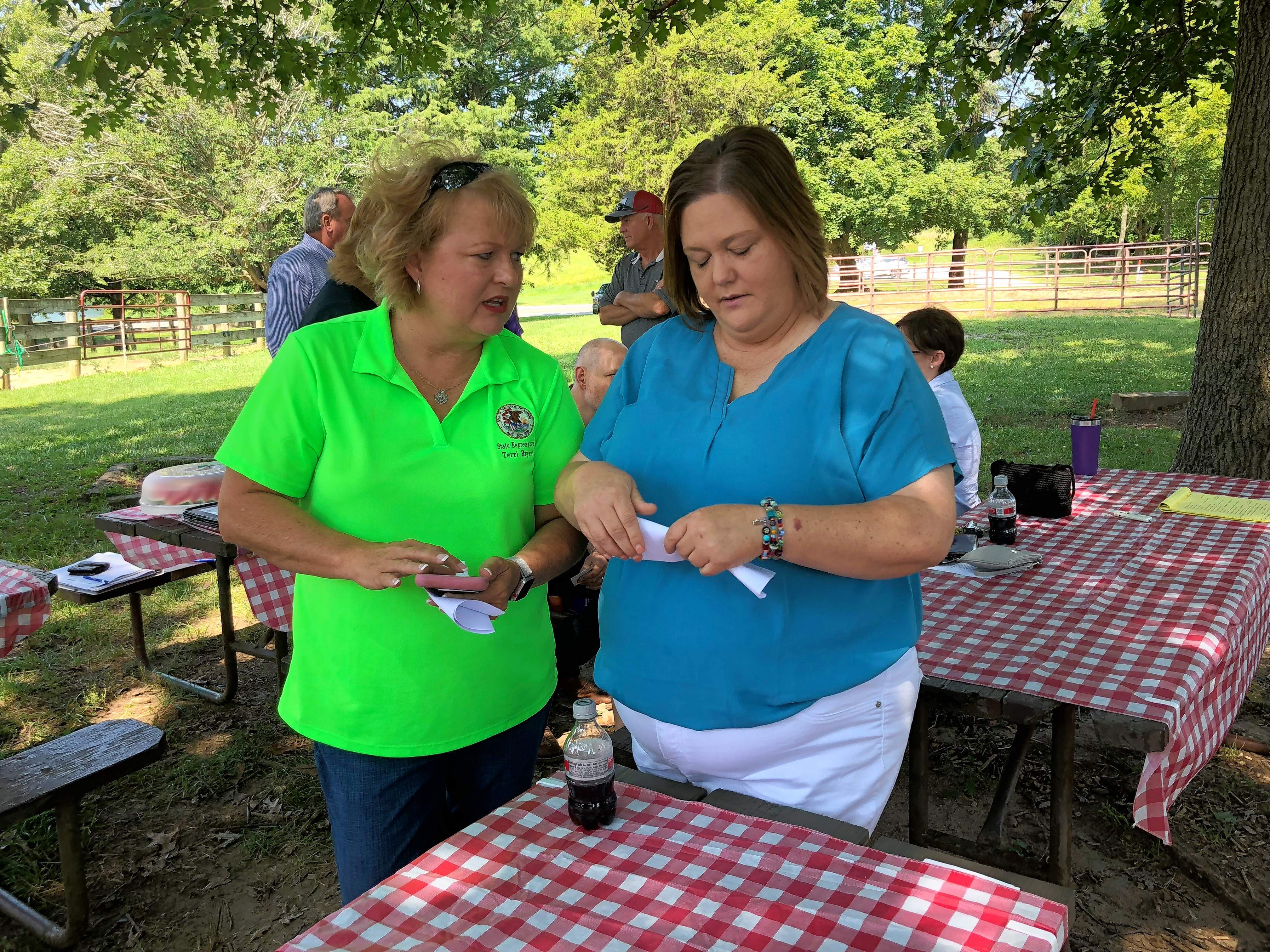 State Rep. Terri Bryant, right, and Stephanie Brown discuss how equine therapy has benefitted Brown's son, Mason, who has autism.