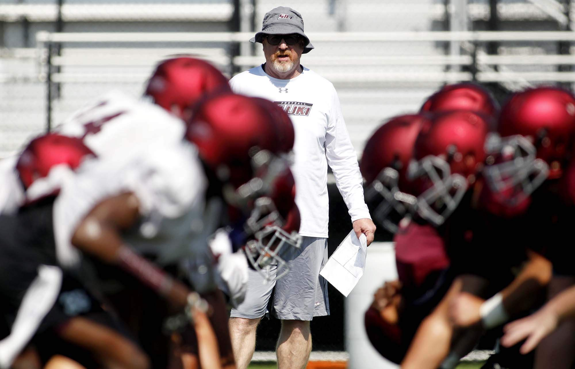 Southern Illinois University defensive head coach Kraig Paulson watches over a drill during the Salukis' practice Friday in Carbondale. Paulson is in his third year as defensive head coach and each of the past two seasons, SIU's defense has been 3.5 points better. This year's de- fense features two players that were on the Missouri Valley Footall Preason All-Conference Team.Defense