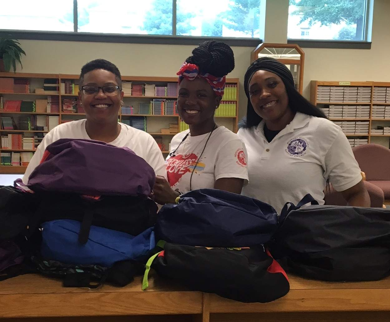 Photo submitted by the Rev. Chris Swims Toni Hughes, Ja'neraa Nelson and Alex Trigg, volunteers from Hopewell Missionary Baptist Church of Carbondale, gather Tuesday to pass out free backpacks and supplies to Carbondale Elementary School students.