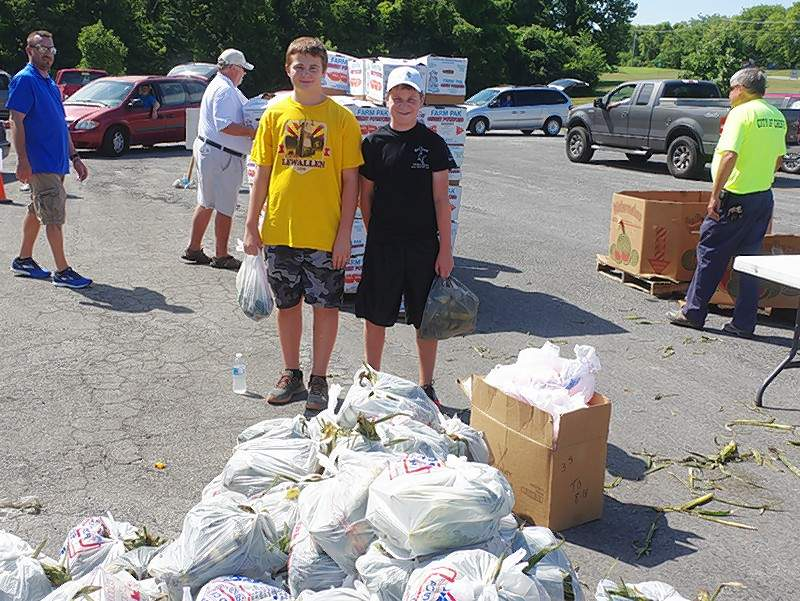 Blake Zappa, left, and Jarrett James, both Chester High School sophomores, prepare to hand out food items as the clientele drive past the distribution point. The boys volunteered to assist food pantry staff with the July Mobile Market.
