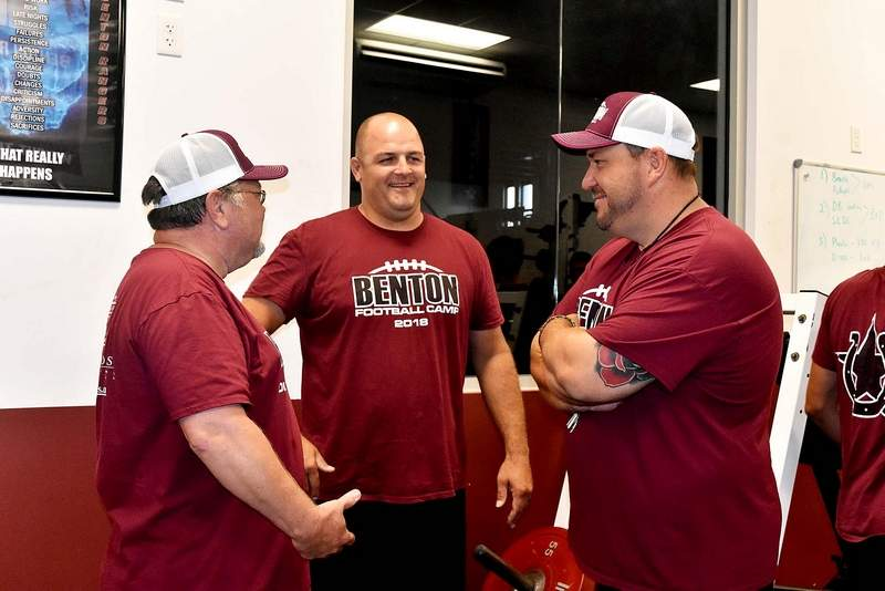 Benton High School head football coach Justin Groves, far right, has a discussion with trainer Jim Sargent and defensive coordinator Casey McCommons during a recent weight room training session at Rich Herrin Gym. The Rangers open the season Friday at Carterville.
