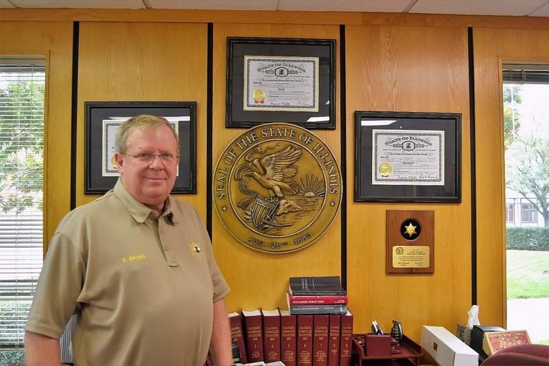 Retired Saline County Sheriff Keith Brown stands at his desk Friday. Brown officially resigned his position Sunday.