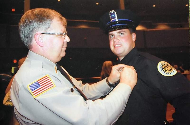 Newly retired Saline County Sheriff Keith Brown pins his son Cameron's badge for Cameron's acceptance into the Nashville Metro Police.