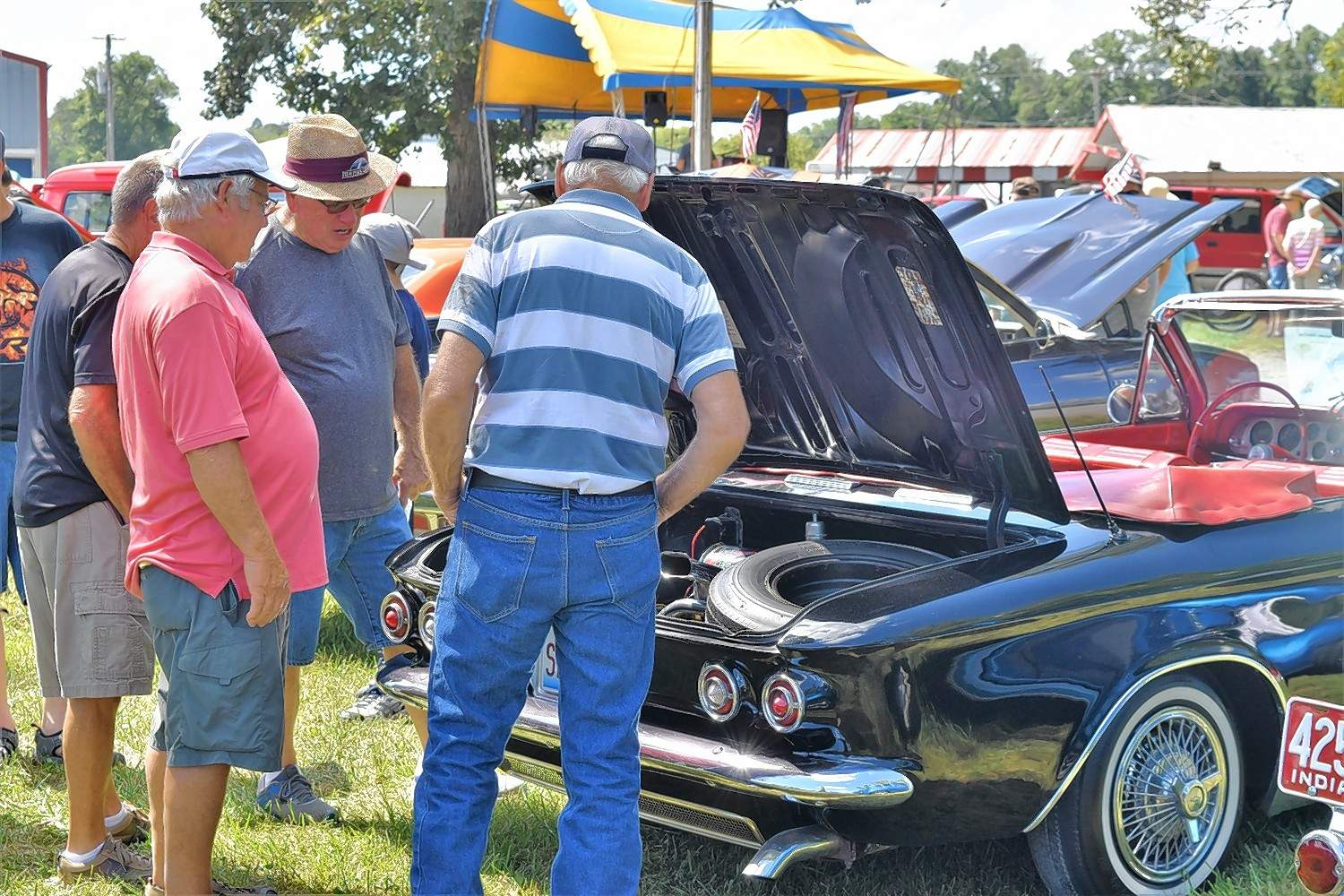 A group  of car enthusiasts inspect the trunk of a car on display.