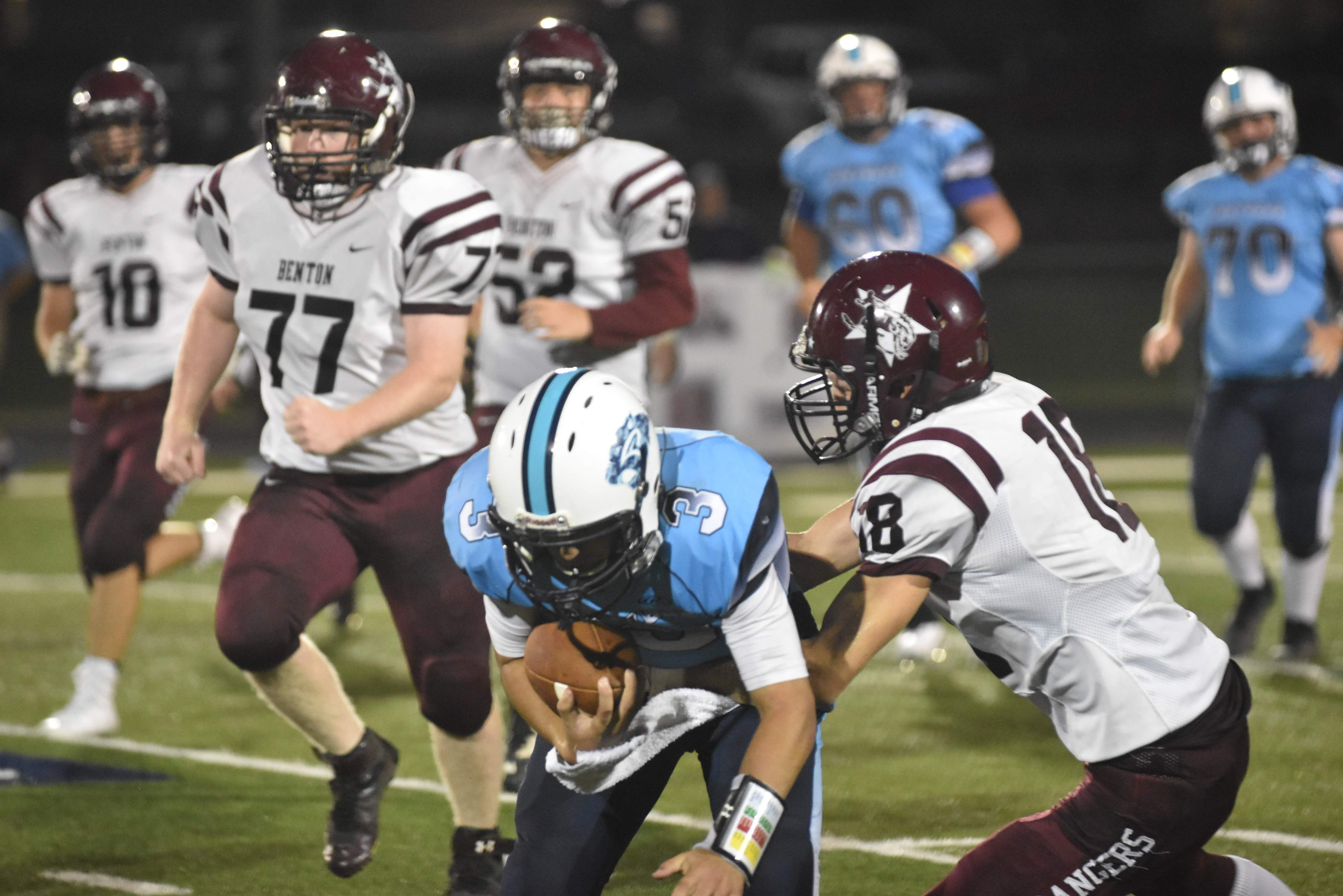 Pinckneyville quarterback Hunter Riggins runs for a short gain while being tackled by Benton's Joey Craig during a prep football game at Pinckneyville on Friday night. The Panthers edged out the Rangers, 23-20.