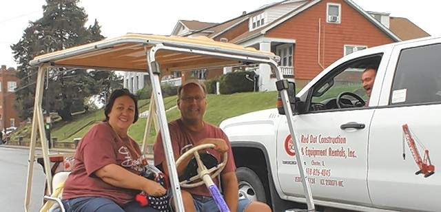 Tammi and Kurt Schroeder of red Dot Construction talk with Craig Rust, driving Red Dot truck, at the 39th Annual Popeye Picnic parade.