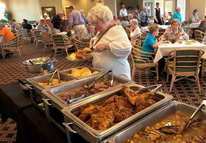 "Jo Davis fills her plate in the buffet line during Saturday's ""Farmers Market Buffet"" at Marion's Kokopelli Golf Club."