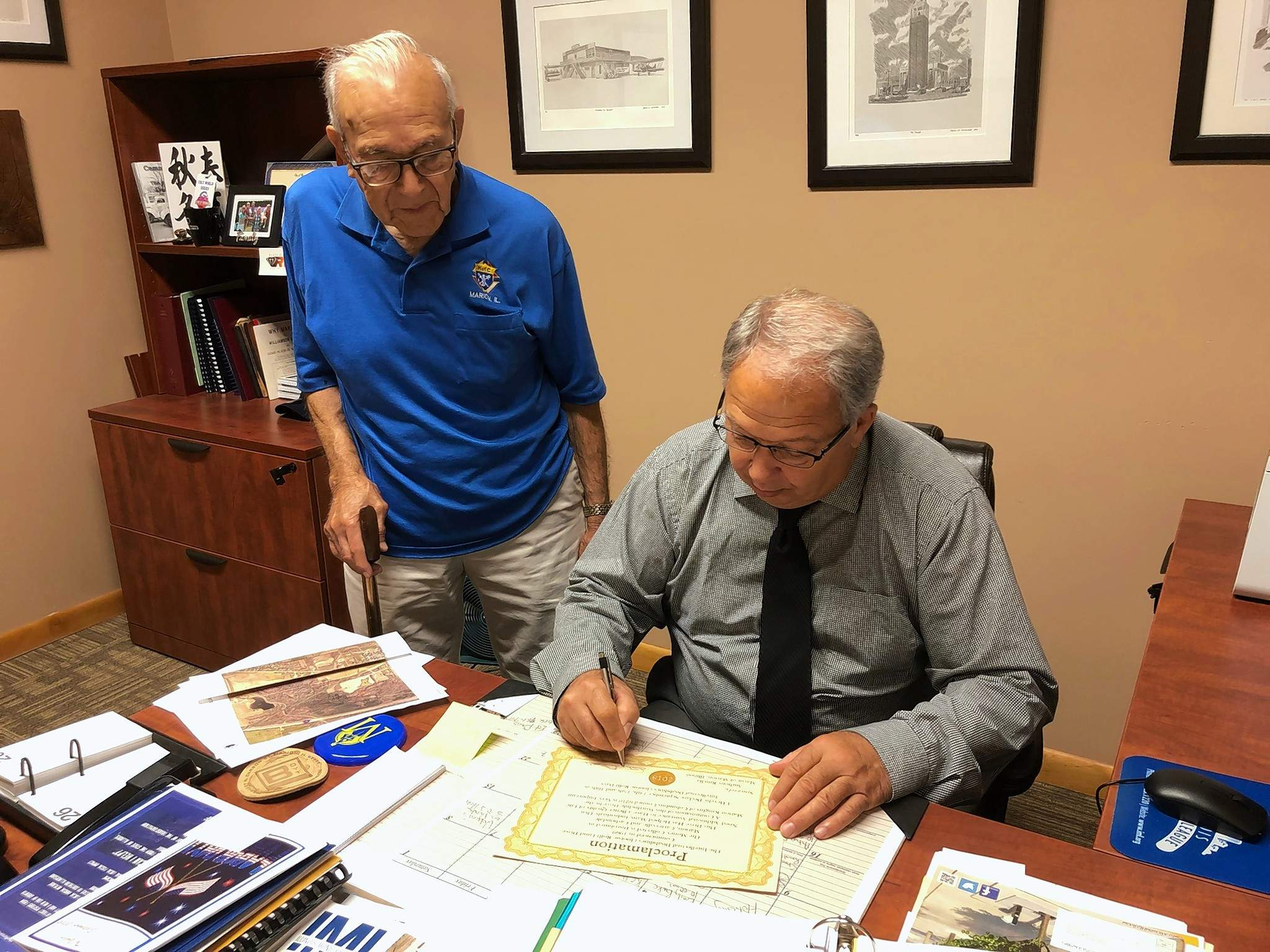 "Tony Sena watches Marion Mayor Anthony Rinella sign a proclamation declaring this weekend ""Tootsie Roll Days"" in Marion."