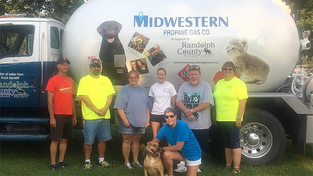 Members of Midwestern Propane Gas stand by the company's new tanker truck, which is dedicated to aid the Randolph County Humane Shelter. From left are Dave Hargis, driver; Jeff Britt; Shelley Evans; Jessica Whittom; Preston Glodo; Denise Wilson; Marybeth Whittom and Daisey.
