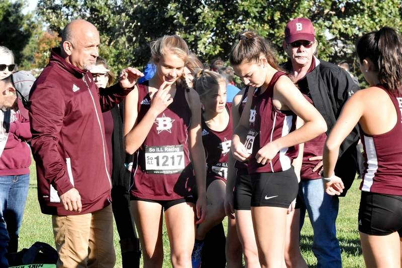 Benton High School coach Brent McLain talks to some of the female runners, from left, Hailey Wallace, Peyton Tieffel, Addyson Miller and Mia McLain before the start of the girls conference cross country meet at Carterville.