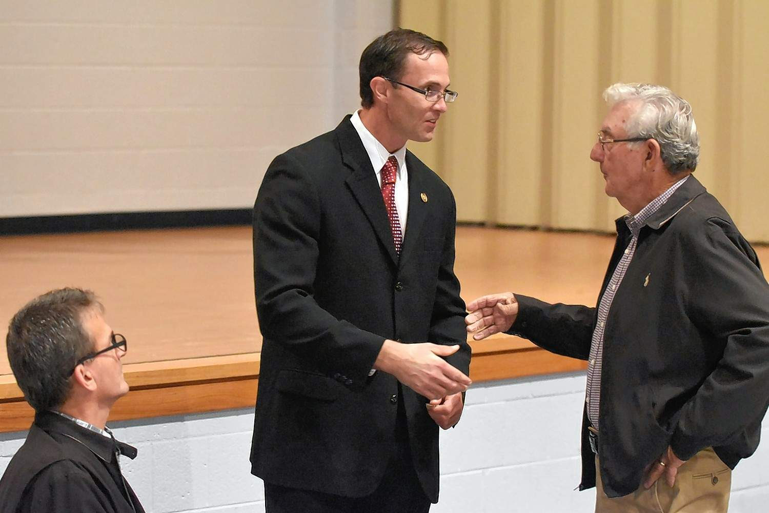 Southeastern Illinois College student government co-adviser Matt Lees, center, explains the rules of a coin flip to decide speaking order, with Saline County Democratic Party Chairman Bob Oglesby, at right, and current Saline County Board chairman Jay Williams.