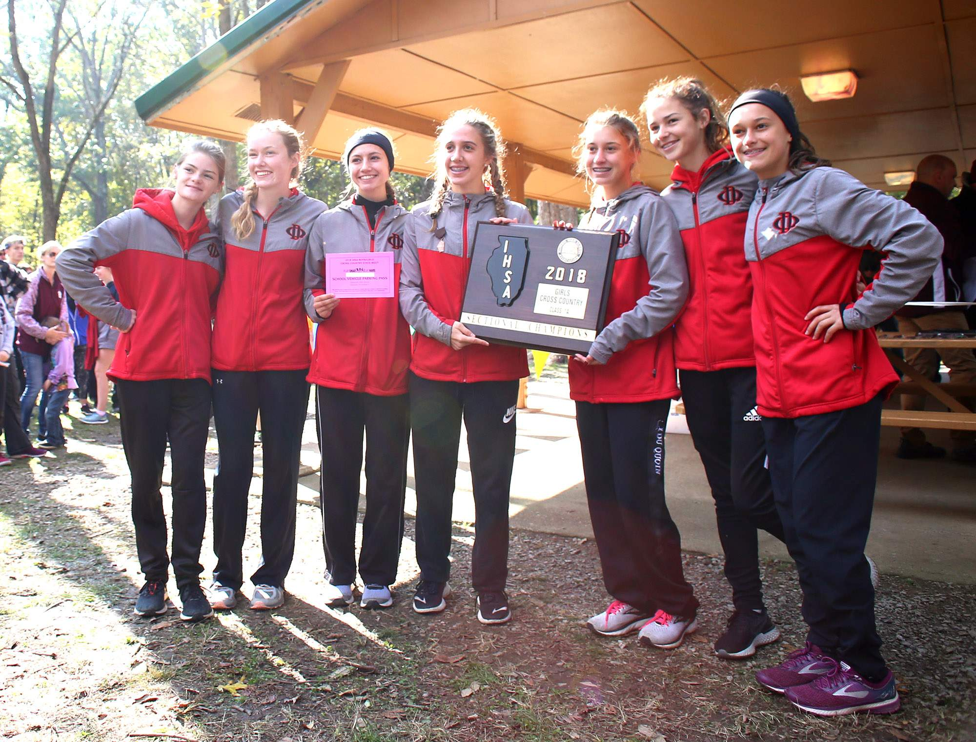 The Du Quoin High School girls cross country team accepts the Benton 1A Sectional championship plaque Saturday.