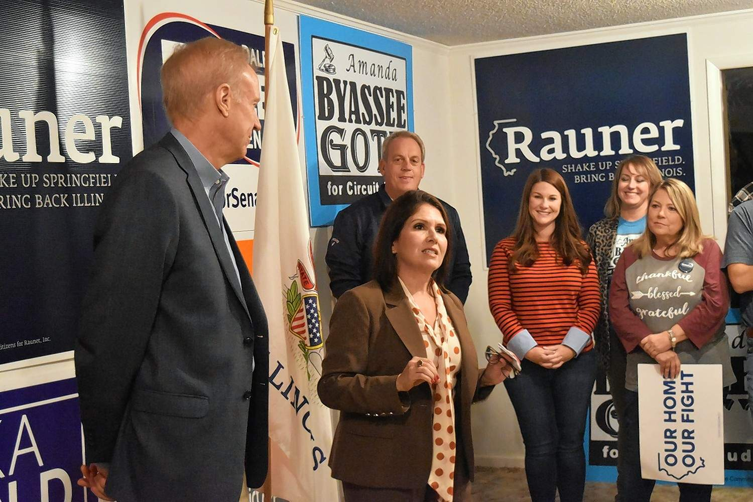 Lt. Gov. Evelyn Sanguinetti, with Gov. Bruce Rauner, left, speaks at a Harrisburg rally on Friday night.