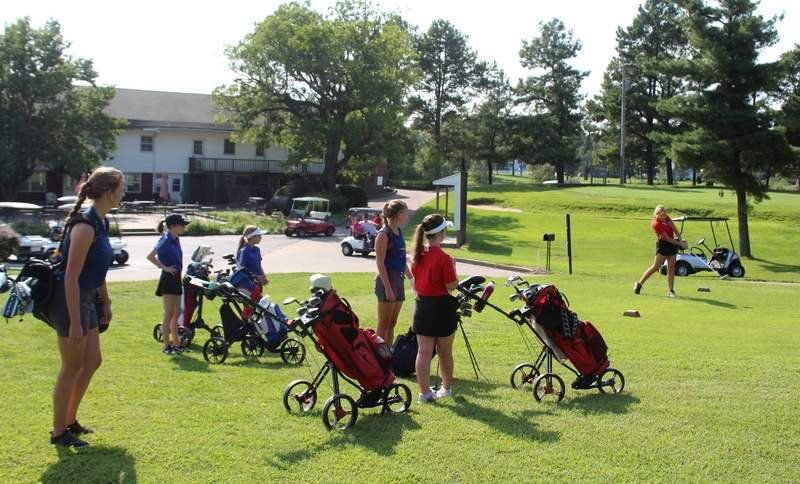 Golfers practice shots off the tee at Red Hawk Golf Course.