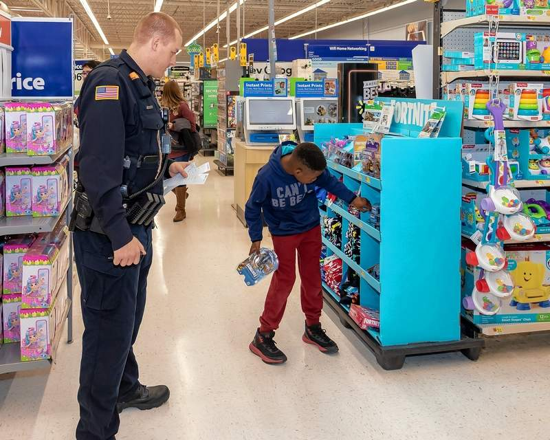 Du Quoin Police Officer Josh Cushman helps Malik Thomas, age 10, of Du Quoin, with a selection.