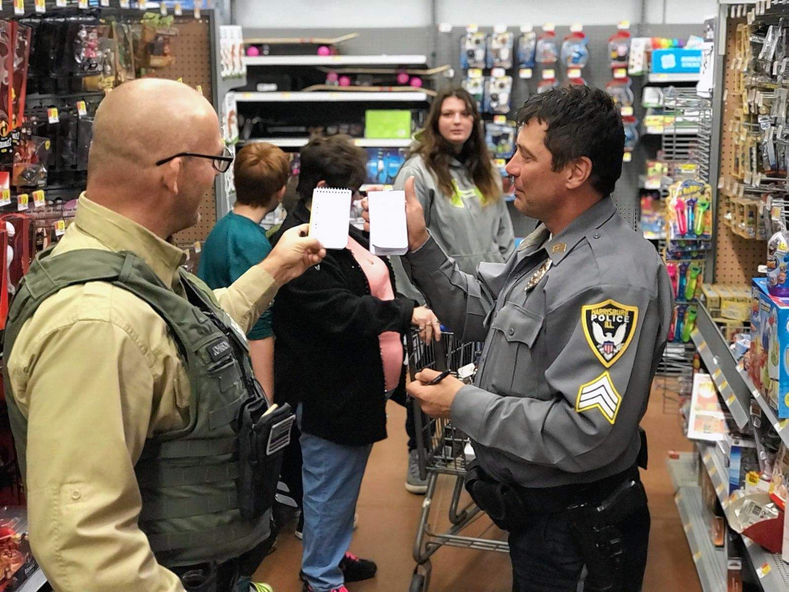"""Saline County Sheriff James """"Whipper"""" Johnson, left, and Harrisburg Police Department Sgt. Curt Hustedde compare shopping lists as they assist with Saline County's Shop with a Cop program Saturday at the Harrisburg Walmart."""
