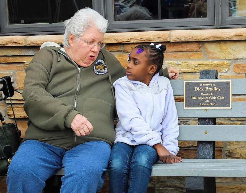 Ellen Bradley shares a moment Tuesday at Hickory Ridge Golf Course with 6-year-old Khloe Ford, a member of the Boys and Girls Club of Carbondale. The two are sitting on the recycled plastic bench first envisioned by Bradley's late husband, Dick Bradley.