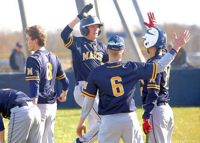 Marion's Austin Palmer is greeted at the dugout after scoring the game's first run Friday against Murphysboro.