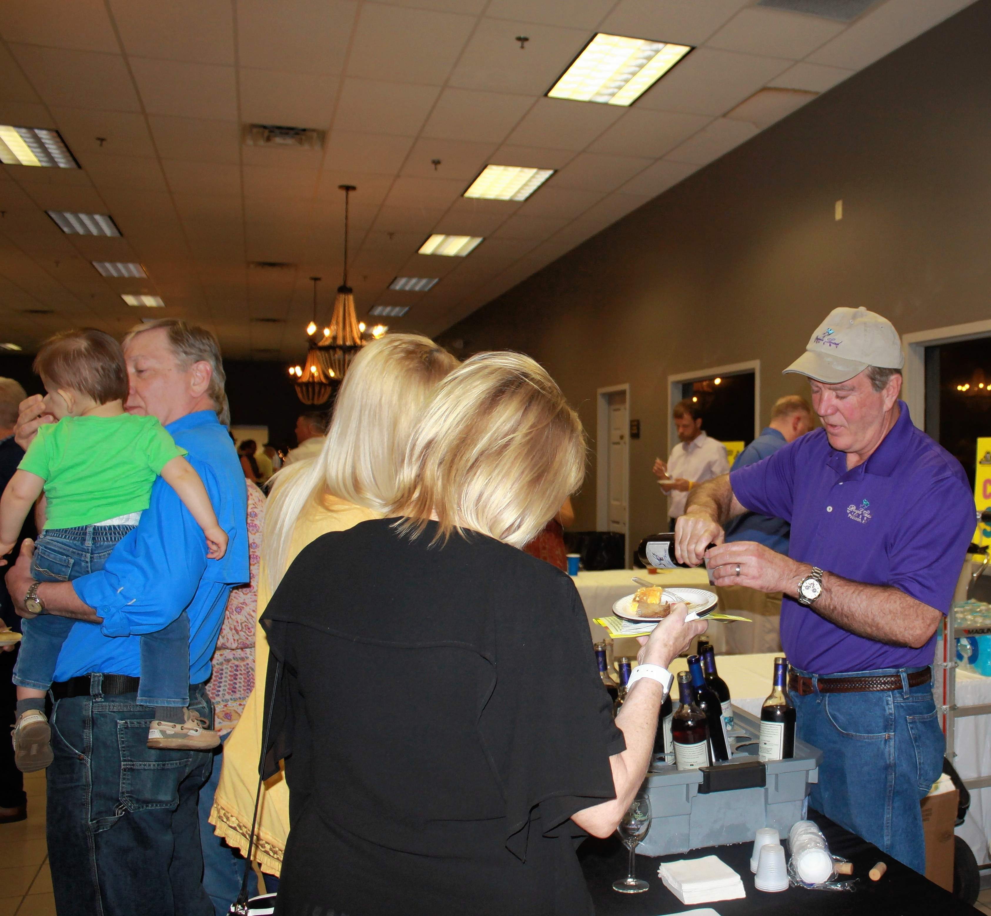 A server for Purple Toad Winery of Paducah, Kentucky pours a sample. Purple Toad has attended Taste of SI for the past three years. This year,  they offered a variety of wines including their Red Sangria, Lauren's Blackberry, and Paducah Harbor.