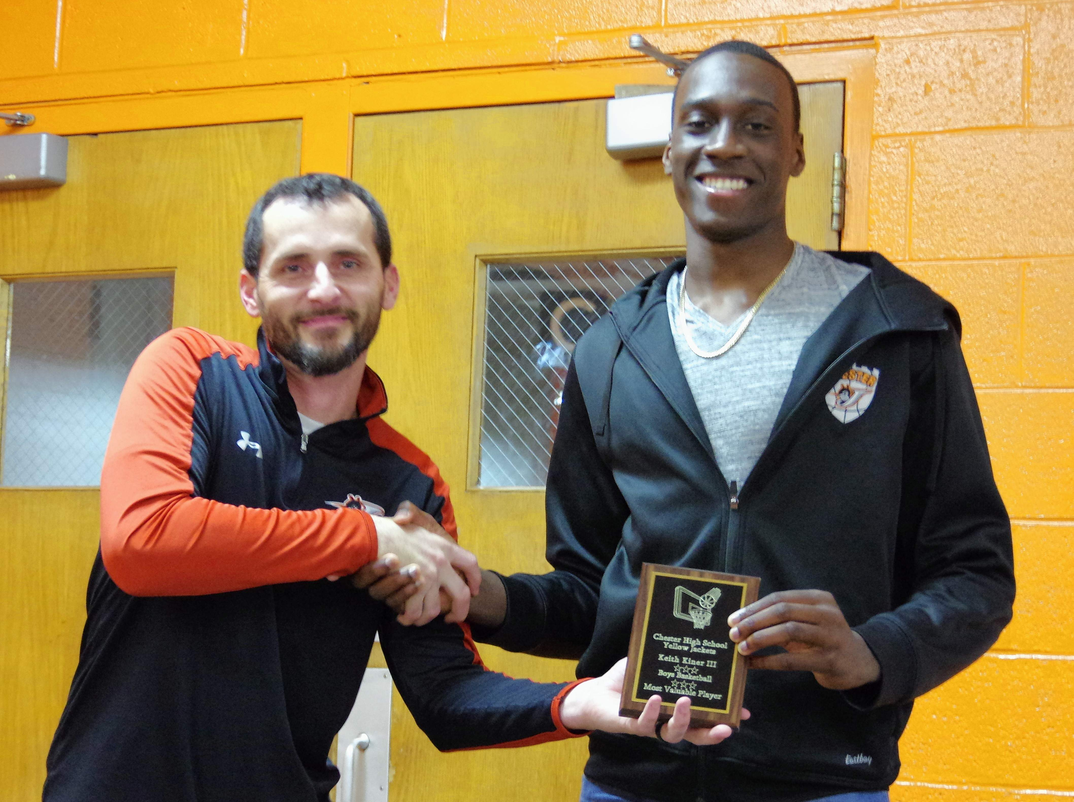 """Head Coach Brad Norman, left, presents Keith Kiner III with the """"Player of the Year"""" plaque."""