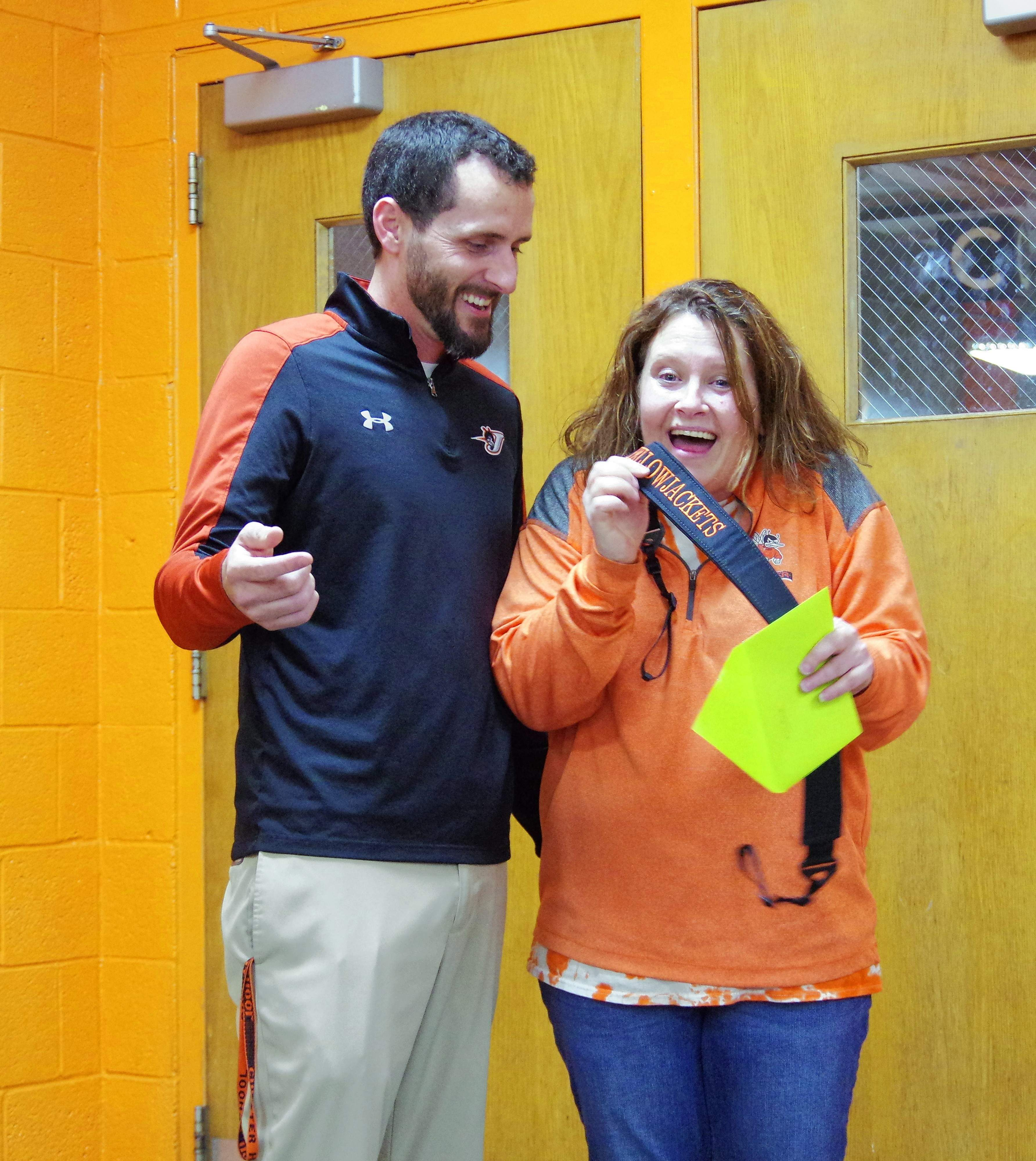 Misti Price is delighted with the camera strap given to her by Coach Brad Norman. Price started and maintained the boys basketball web site and Facebook page, and is at every game, camera in hand.